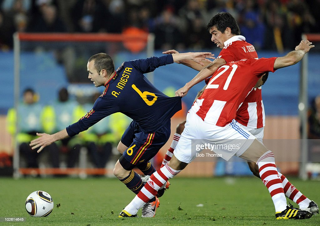 Andres Iniesta of Spain has his shirt pulled by Victor Caceres of Paraguay during the 2010 FIFA World Cup South Africa Quarter Final match between Paraguay and Spain at Ellis Park Stadium on July 3, 2010 in Johannesburg, South Africa. Spain won the match 1-0.