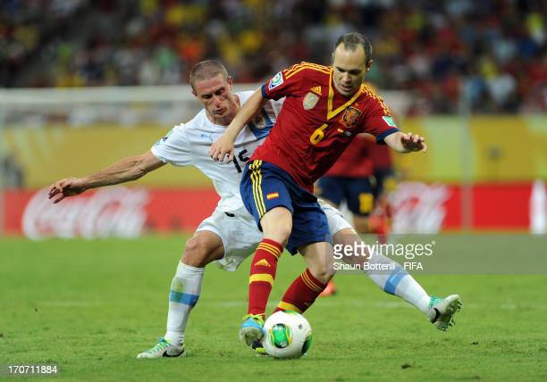 Andres Iniesta of Spain holds off Diego Perez of Uruguay during the FIFA Confederations Cup Brazil 2013 Group B match between Spain and Uruguay at...