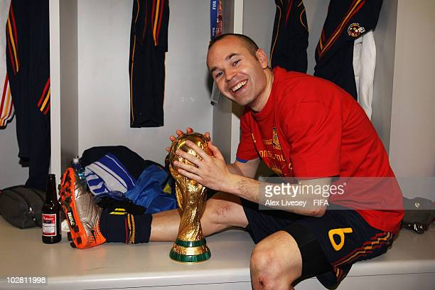 Andres Iniesta of Spain holds the trophy in the Spanish dressing room after they won the 2010 FIFA World Cup at Soccer City Stadium on July 11 2010...