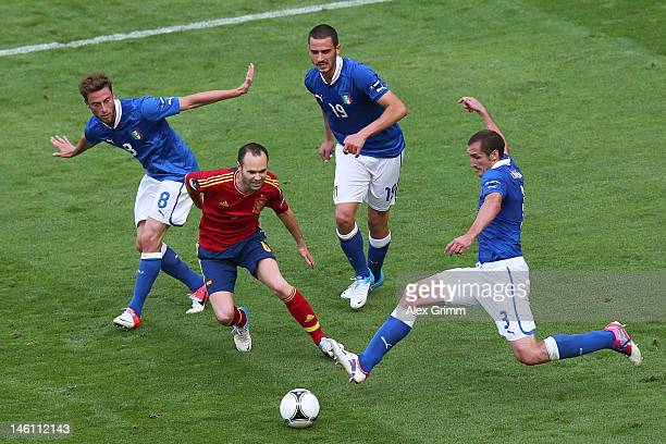 Andres Iniesta of Spain is closed down by Claudio Marchisio Leonardo Bonucci and Giorgio Chiellini of Italy during the UEFA EURO 2012 group C match...