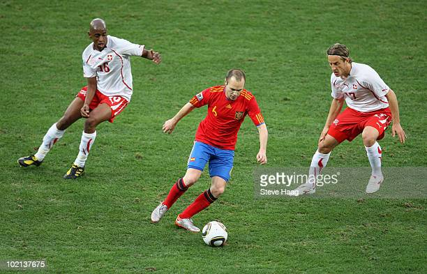 Andres Iniesta of Spain is closed down by Gelson Fernandes and Reto Ziegler of Switzerland during the 2010 FIFA World Cup South Africa Group H match...