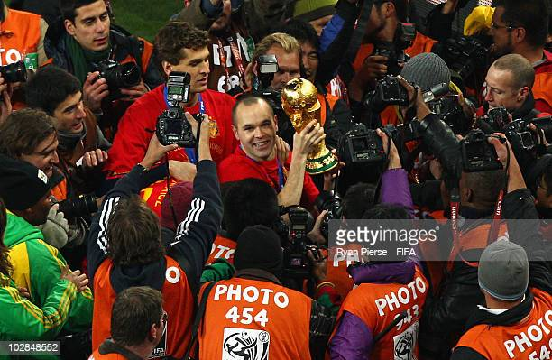Andres Iniesta of Spain is surrounded by photographers as he celebrates with the World Cup after the 2010 FIFA World Cup South Africa Final match...