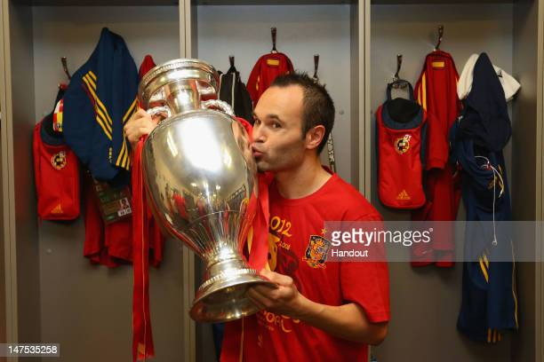 Andres Iniesta of Spain poses in the dressing room with the trophy following the UEFA EURO 2012 final match between Spain and Italy at the Olympic...