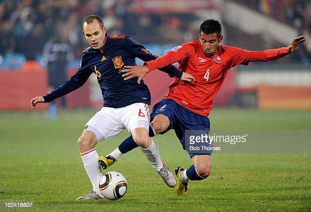 Andres Iniesta of Spain protects the ball as Mauricio Isla of Chile attempts a tackle during the 2010 FIFA World Cup South Africa Group H match...