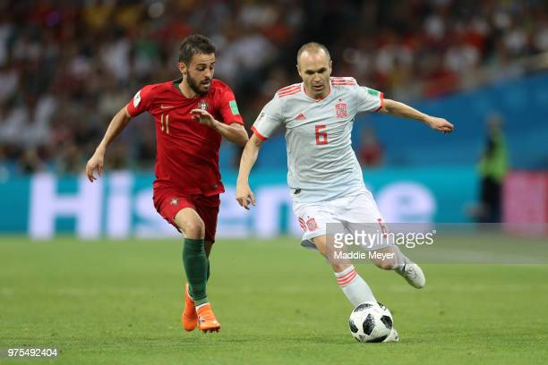 Andres Iniesta of Spain runs with the ball under pressure from Bernardo Silva of Portugal during the 2018 FIFA World Cup Russia group B match between...