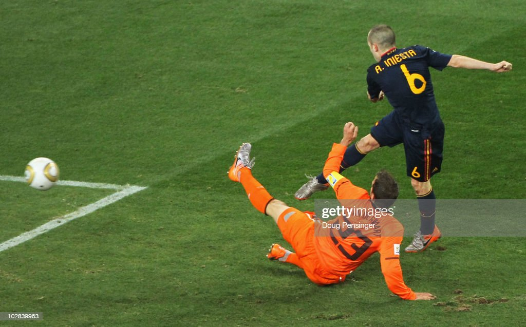 Andres Iniesta of Spain scores the opening goal as Rafael Van der Vaart of the Netherlands tries to defend during the 2010 FIFA World Cup South Africa Final match between Netherlands and Spain at Soccer City Stadium on July 11, 2010 in Johannesburg, South Africa.