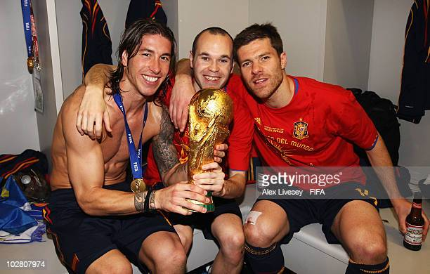 Andres Iniesta Sergio Ramos and Xabi Alonso of Spain pose with the trophy in the Spanish dressing room after they won the 2010 FIFA World Cup at...