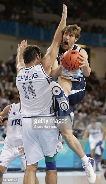 Andres Nocioni of Argentina drives to the basket against Roberto Chiacig of Italy in the men's basketball preliminary game between Italy and...