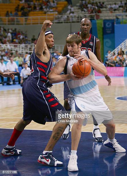 Andres Nocioni of Argentina moves to drive past Shawn Marion of United States in the first half of the men's basketball semifinal game on August 27...