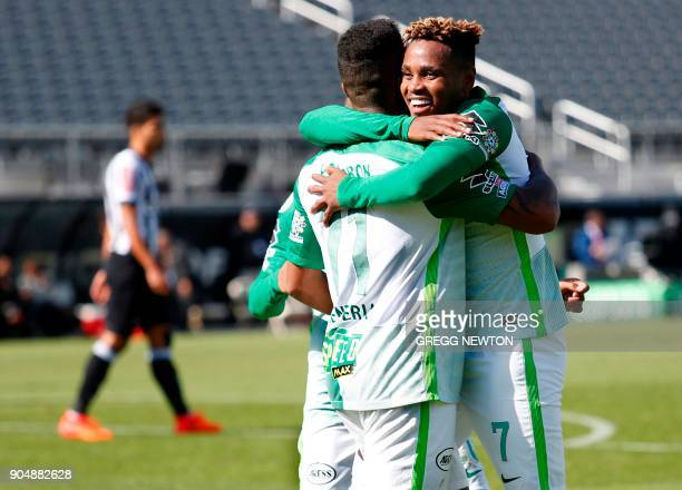 Andres Renteria of Colombian side Atletico Nacional gets a hug from teammate Gustavo Torres after scoring a goal against Brazilian club Atletico...