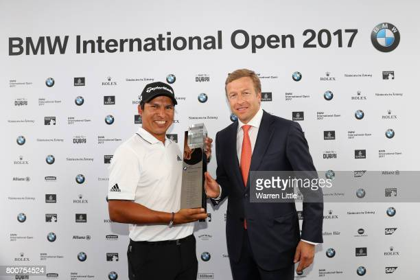 Andres Romero of Argentina receives the trophy from Oliver Zipse of BMW AG following his victory during the final round of the BMW International Open...