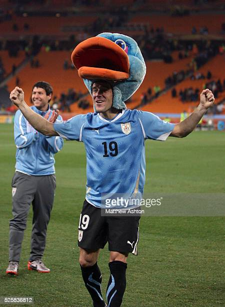 Andres Scott of Uruguay celebrates progressing through to the semifinals wearing the head of a fancy dress outfit given to him by a Uruguay fan