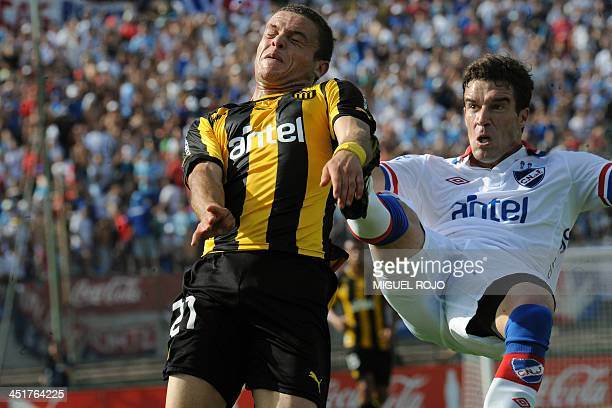 Andres Scotti of Uruguay's Nacional vies for the ball with Penarol's Jonathan Rodriguez during their Uruguayan first division football derby at the...