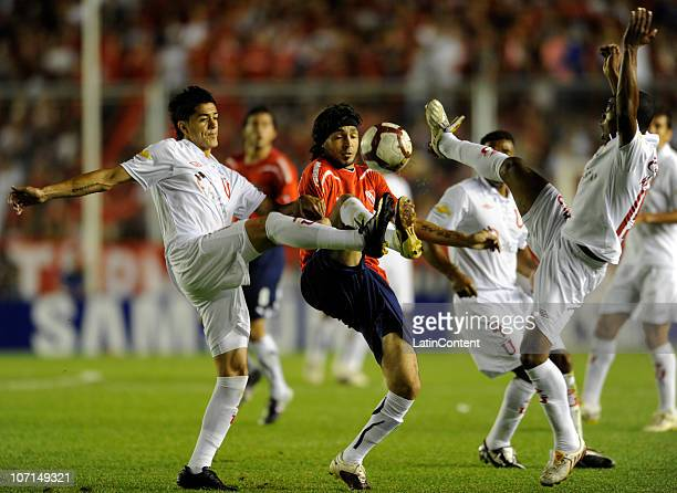 Andres Silvera of Independiente struggles for the ball with Norberto Araujo and William Araujo of Liga Deportiva Universitaria during a match as part...