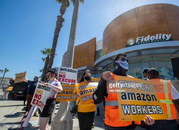 Andres Tinaje, right, joins other supporters of Amazon workers protesting outside of Fidelity Investments in Santa Monica. The protest was held...