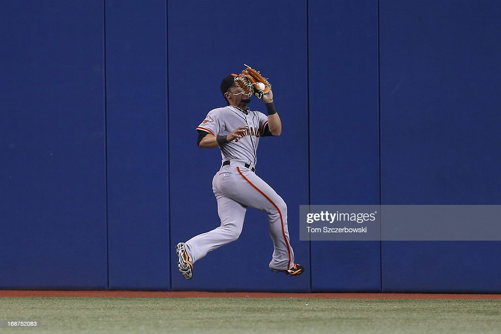Andres Torres #56 of the San Francisco Giants catches a fly ball in the seventh inning during MLB game action against the Toronto Blue Jays on May 14, 2013 at Rogers Centre in Toronto, Ontario, Canada.
