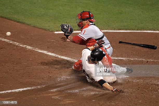 Andres Torres of the San Francisco Giants slides safely under the legs of Carlos Ruiz of the Philadelphia Phillies to score a run in the in the fifth...