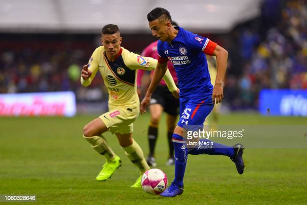 Andres Uribe of America and Roberto Alvarado of Cruz Azul fight for the ball during a 14th round match between Cruz Azul and America as part of...