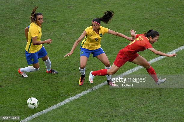 Andressa Alves of Brazil battles for the ball against Haiyan Wu of China during the Women's Group E first round match between Brazil and China PR...