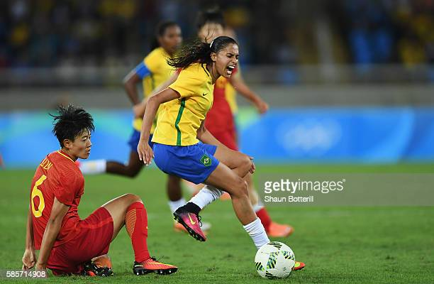 Andressa Alves of Brazil is challenged by Dongna Li of China during the Women's Group E first round match between Brazil and China PR during the Rio...