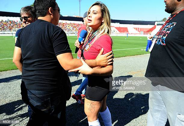 Andressa Urach , a former contestant in Brazil's Miss BumBum pageant is escorted out of the Portugal team training ground in Campinas, Sao Paulo, on...