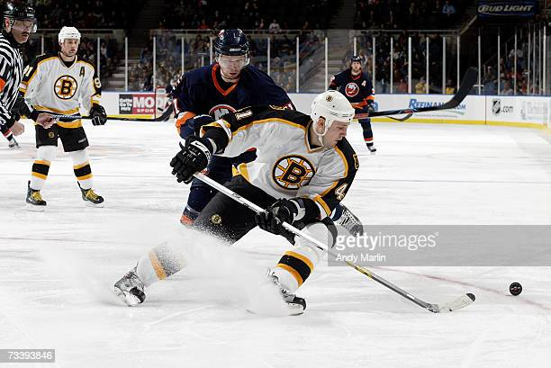 Andrew Alberts of the Boston Bruins skates with the puck against Andy Hilbert of the New York Islanders at Nassau Coliseum on February 15 2007 in...