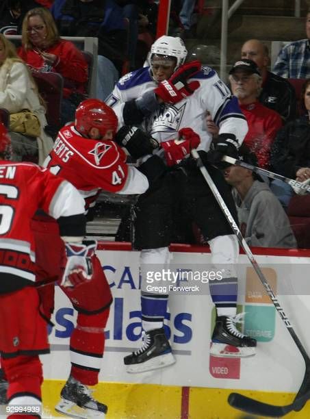 Andrew Alberts of the Carolina Hurricanes checks Wayne Simmonds of the Los Angeles Kings into the boards during an NHL game on November 11, 2009 at...