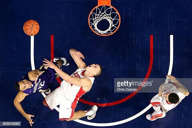 Andrew Andrews of the Washington Huskies runs in to Kaleb Tarczewski of the Arizona Wildcats during the second half of the college basketball game at...