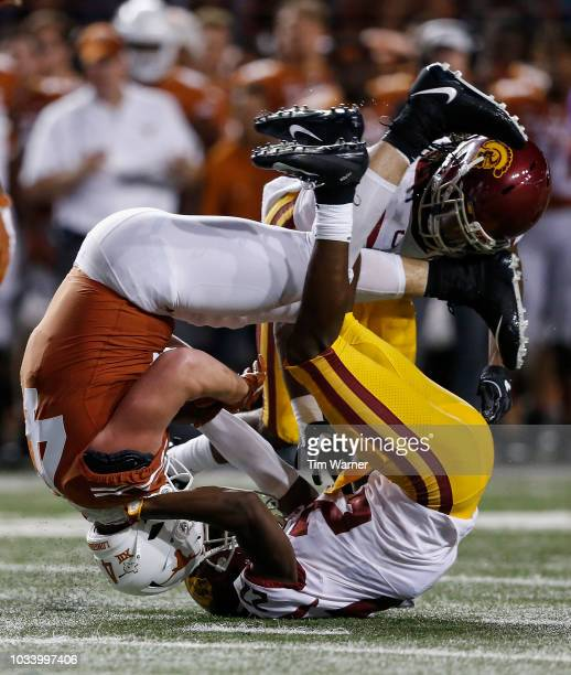 Andrew Beck of the Texas Longhorns is tackled by Ajene Harris of the USC Trojans and Marvell Tell III in the second half at Darrell K RoyalTexas...