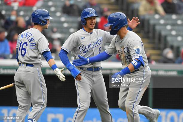 Andrew Benintendi and Nicky Lopez celebrate with Whit Merrifield of the Kansas City Royals after Lopez and Merrifield scored on a home run by...