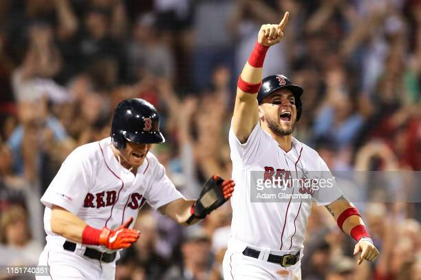 Andrew Benintendi celebrates after he scores the game-wining run with Michael Chavis on a walk-off single by hit Marco Hernandez of the Boston Red...