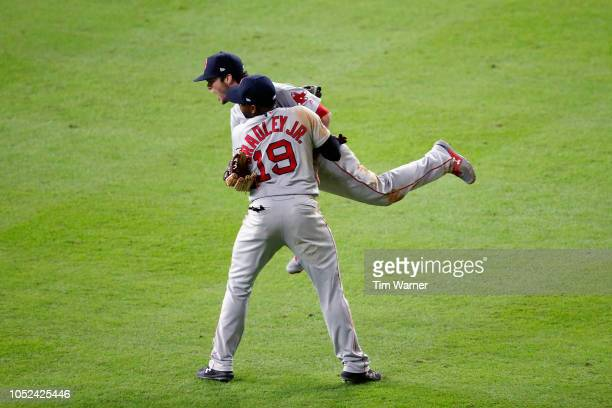 Andrew Benintendi celebrates with Jackie Bradley Jr #19 of the Boston Red Sox after Benintendi caught a line drive hit by Alex Bregman of the Houston...