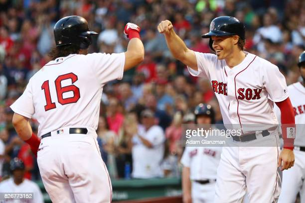 Andrew Benintendi high fives Brock Holt of the Boston Red Sox after hitting a tworun home run in the first inning of a game against the Chicago White...