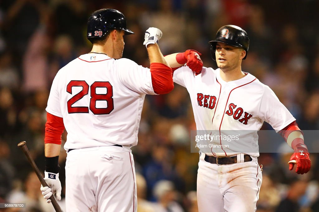Andrew Benintendi #16 high fives J.D. Martinez #28 of the Boston Red Sox after hitting a solo home run in the fifth inning of a game against the Oakland Athletics at Fenway Park on May 15, 2018 in Boston, Massachusetts.