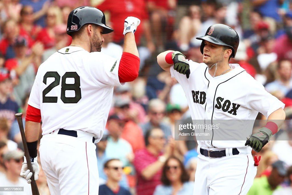 Andrew Benintendi #16 high fives J.D. Martinez #28 of the Boston Red Sox after hitting a solo home run in the fourth inning of a game against the Atlanta Braves at Fenway Park on May 26, 2018 in Boston, Massachusetts.
