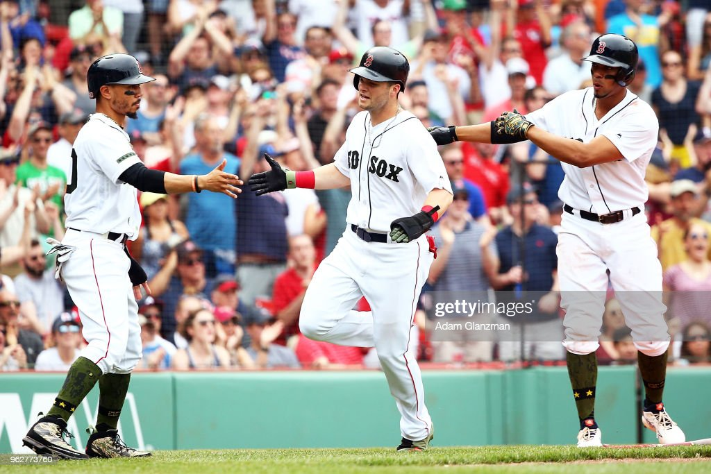 Andrew Benintendi #16 high fives Mookie Betts #50 of the Boston Red Sox after the y both scored in the sixth inning of a game against the Atlanta Braves at Fenway Park on May 26, 2018 in Boston, Massachusetts.