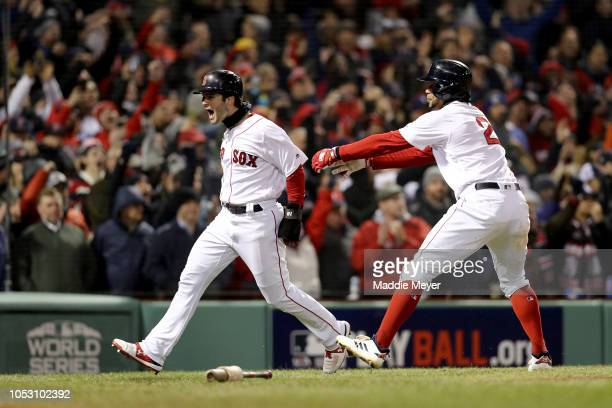 Andrew Benintendi is congratulated by his teammate Xander Bogaerts of the Boston Red Sox after scoring a fifth inning run against the Los Angeles...