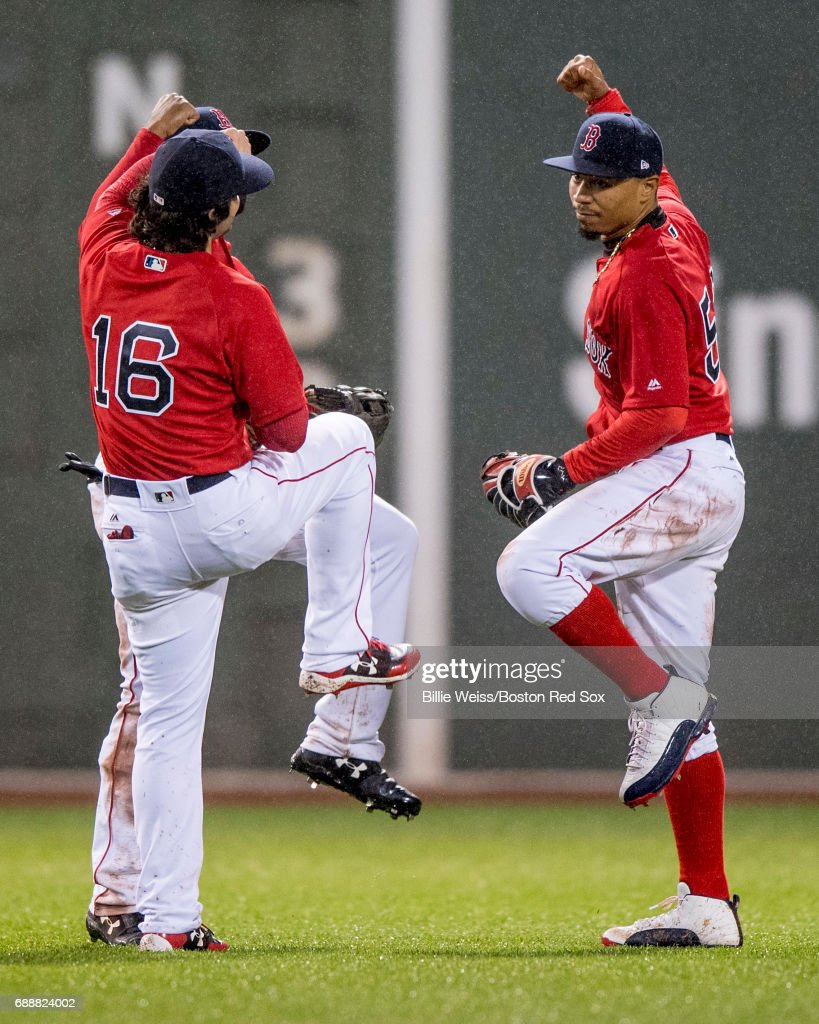 Andrew Benintendi #16, Jackie Bradley Jr. #18, and Mookie Betts #50 of the Boston Red Sox celebrate a victory against the Seattle Mariners on May 26, 2017 at Fenway Park in Boston, Massachusetts.
