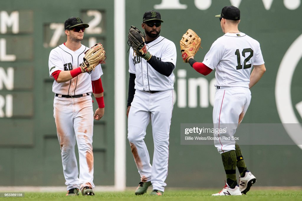 Andrew Benintendi #16, Jackie Bradley Jr. #19, and Brock Holt #12 of the Boston Red Sox celebrate a victory against the Toronto Blue Jays on May 28, 2018 at Fenway Park in Boston, Massachusetts.