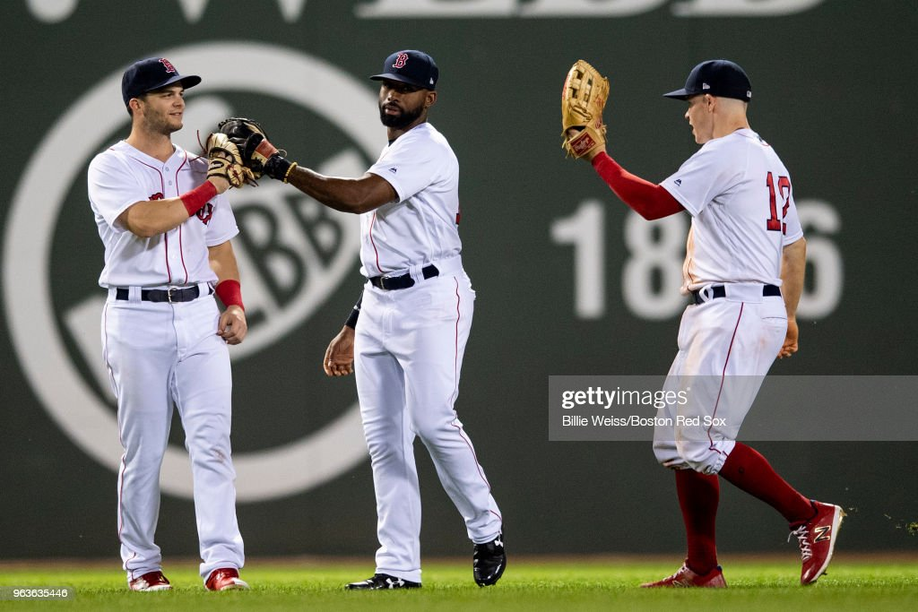 Andrew Benintendi #16, Jackie Bradley Jr. #19, and Brock Holt #12 of the Boston Red Sox celebrate a victory against the Toronto Blue Jays on May 29, 2018 at Fenway Park in Boston, Massachusetts.