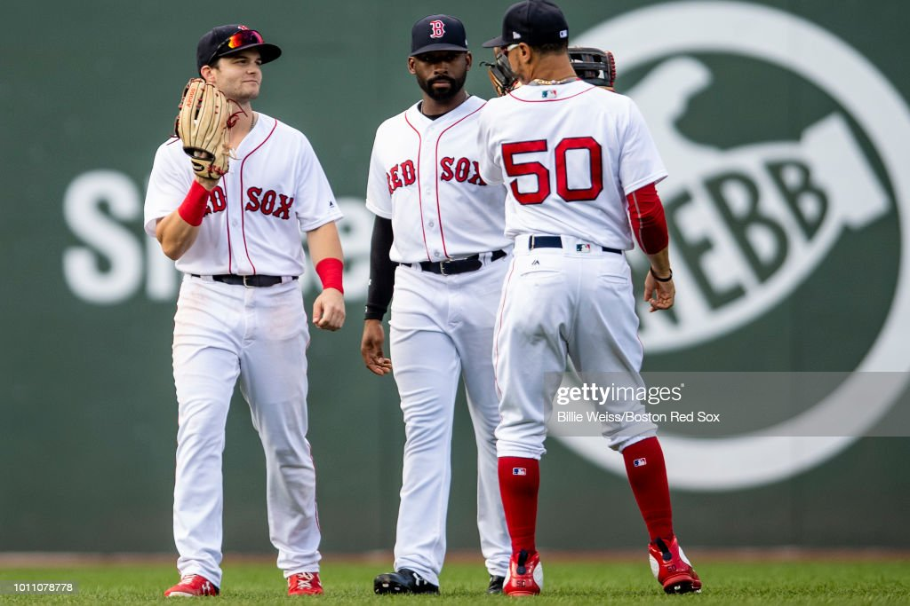 Andrew Benintendi #16, Jackie Bradley Jr. #19, and Mookie Betts #50 of the Boston Red Sox celebrate a victory against the New York Yankees on August 4, 2018 at Fenway Park in Boston, Massachusetts.