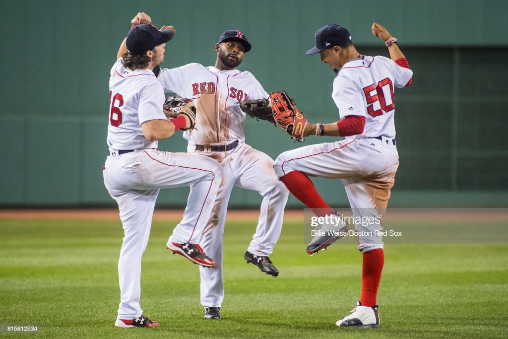 Andrew Benintendi #16, Jackie Bradley Jr. #19, and Mookie Betts #50 of the Boston Red Sox celebrate a victory against the New York Yankees on July 16, 2017 at Fenway Park in Boston, Massachusetts.