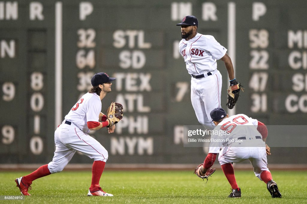 Andrew Benintendi #16, Jackie Bradley Jr. #19, and Mookie Betts #50 of the Boston Red Sox celebrate a victory against the Toronto Blue Jays on September 6, 2017 at Fenway Park in Boston, Massachusetts.
