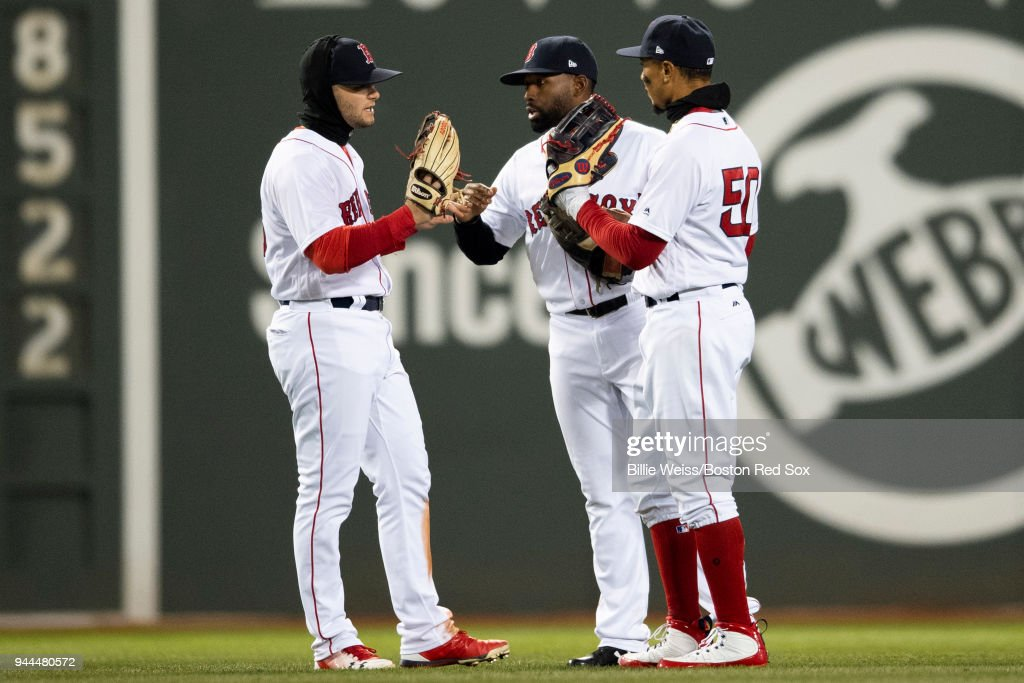 Andrew Benintendi #16, Jackie Bradley Jr. #19, and Mookie Betts #50 of the Boston Red Sox celebrate a victory against the New York Yankees on April 10, 2018 at Fenway Park in Boston, Massachusetts.