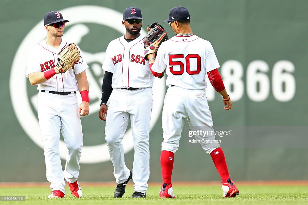 Andrew Benintendi #16, Jackie Bradley Jr. #19 and Mookie Betts #50 of the Boston Red Sox celebrate after a victory over the Baltimore Orioles at Fenway Park on May 20, 2018 in Boston, Massachusetts.