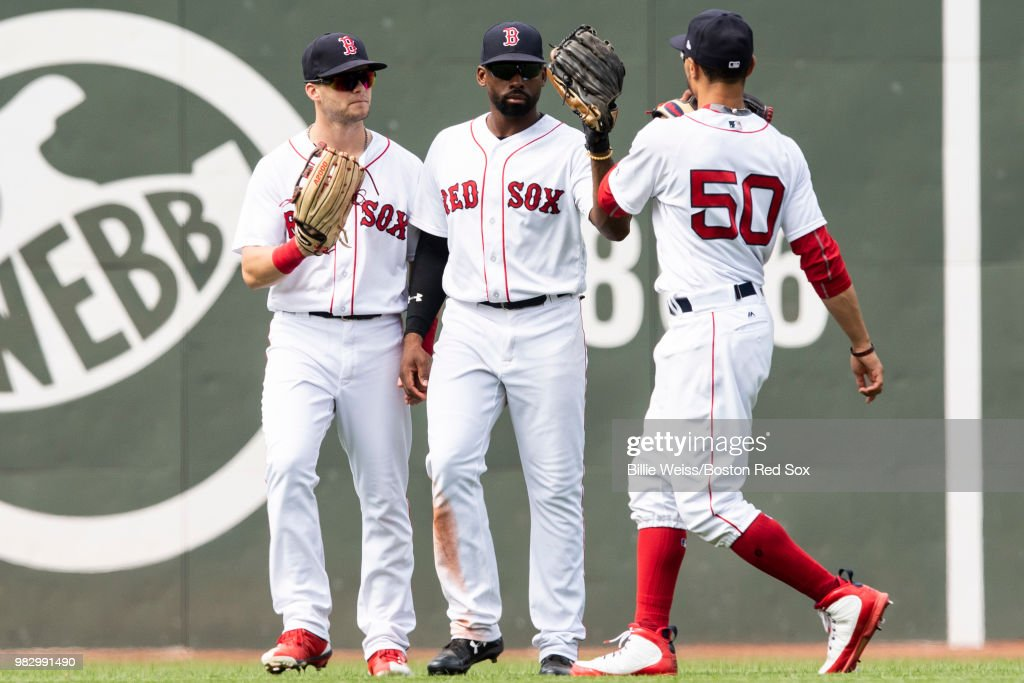 Andrew Benintendi #16, Jackie Bradley Jr. #19, and Mookie Betts #50 of the Boston Red Sox celebrate a victory against the Seattle Mariners on June 24, 2018 at Fenway Park in Boston, Massachusetts.