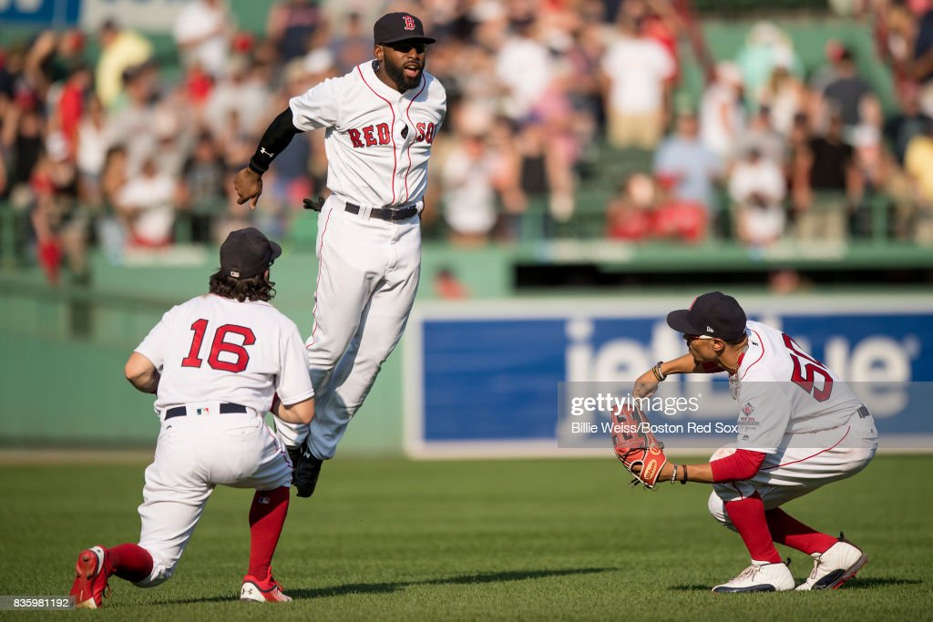 Andrew Benintendi #16, Mookie Betts #50, and Jackie Bradley Jr. #19 of the Boston Red Sox celebrate a victory against the New York Yankees on August 20, 2017 at Fenway Park in Boston, Massachusetts.