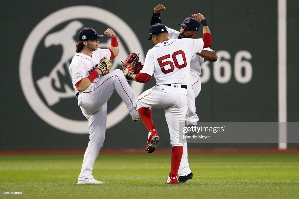 Andrew Benintendi #16, Mookie Betts #50 and Jackie Bradley Jr. #19 of the Boston Red Sox celebrate defeating the Houston Astros 10-3 in game three of the American League Division Series at Fenway Park on October 8, 2017 in Boston, Massachusetts.