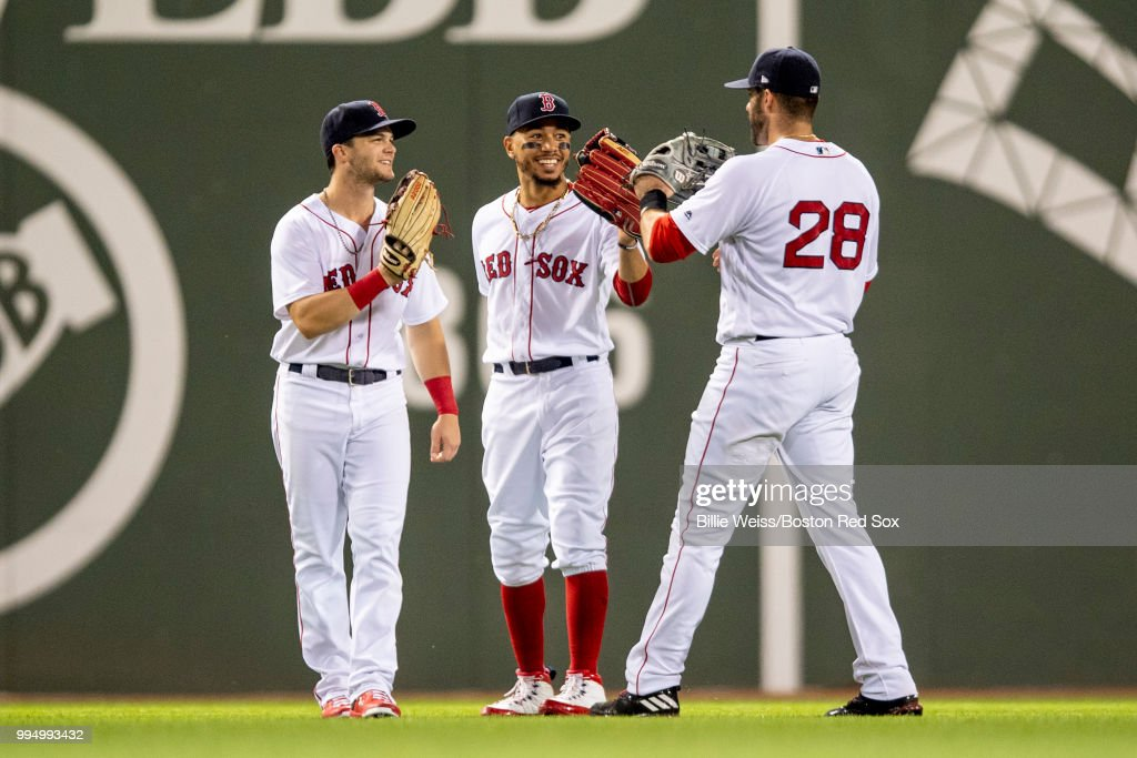 Andrew Benintendi #16, Mookie Betts #50 and J.D. Martinez #28 of the Boston Red Sox celebrate a victory against the Texas Rangers on July 9, 2018 at Fenway Park in Boston, Massachusetts.