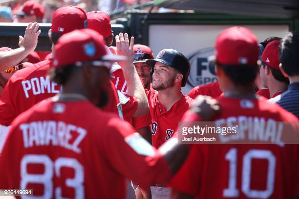 Andrew Benintendi of the Boston Red Sox celebrates his first inning home run with teammates against the St Louis Cardinals during a spring training...